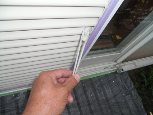 小さな刷毛で雨戸の端を塗る